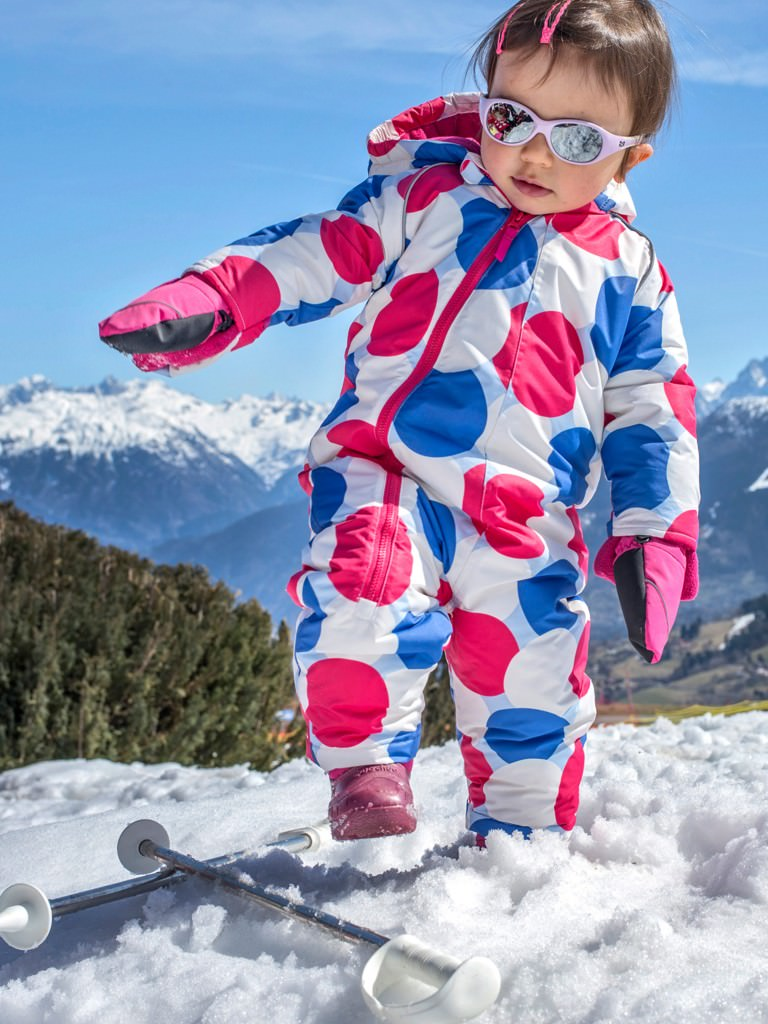 Child enjoying the snow in a ski onesie