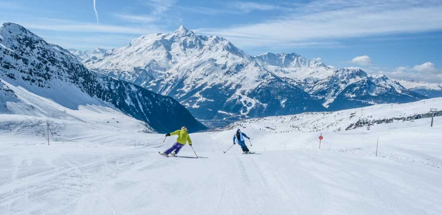A pair of skiers on an open piste with a beautiful mountainous backdrop