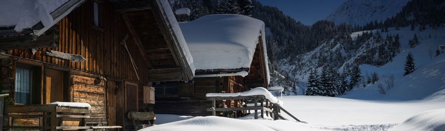 Traditional wooden ski chalet covered in thick snow